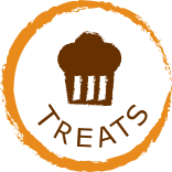 round ligth brown circle jaggered edge with the word treats and muffin centered